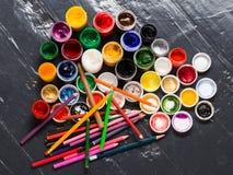 Verschiedene Farben in den Banken, pensils auf dem Boden Stockfotografie