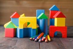 Verschiedene Farben von den Bleistiften ontable mit Bausteinen Stockfotografie