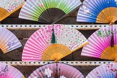Verschiedene Farben von Handfans werden für Verkauf angezeigt lizenzfreies stockfoto
