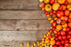 Verschiedene verschiedene Farborganische selbstgezogene Tomaten auf altem hölzernem Lizenzfreie Stockfotos
