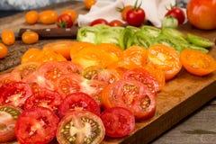 Verschiedene verschiedene Farborganische selbstgezogene Tomaten an Bord schnitt Lizenzfreie Stockbilder