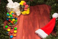 Verschiedene Farbsüßigkeiten auf hölzernem Hintergrund mit Lametta Kopieren Sie Platz Stockfotos