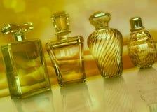 Verschiedene Flaschen Parfüm auf dunklem goldenem Hintergrund Stockfotos