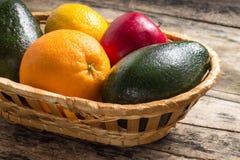 Verschiedene Früchte in der Flechtweide auf hölzernem Hintergrund Stockbild