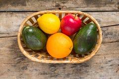 Verschiedene Früchte in der Flechtweide auf hölzernem Hintergrund Stockfotografie