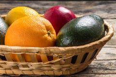 Verschiedene Früchte in der Flechtweide auf hölzernem Hintergrund Stockbilder