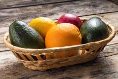 Verschiedene Früchte in der Flechtweide auf hölzernem Hintergrund Lizenzfreie Stockfotos
