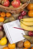 Verschiedene Früchte im Korb mit Bleistift und Buch Stockfotos