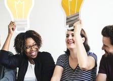 Verschiedene Freunde mit kreativem Konzept der Glühlampenikonen Lizenzfreie Stockfotos