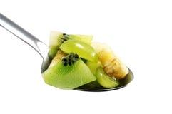 Verschiedene Frucht bessert im Löffel aus, der über Weiß lokalisiert wird Lizenzfreies Stockbild