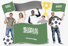 Verschiedene Fußballfane, welche die Flagge von Saudi-Arabien halten lizenzfreies stockbild