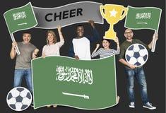 Verschiedene Fußballfane, welche die Flagge von Saudi-Arabien halten stockfotografie