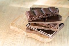 Verschiedene gebrochene Schokoriegel gestapelt auf einem hölzernen Brett Schokolade, beleuchtet durch die Sonne Platz für Text Lizenzfreie Stockfotos