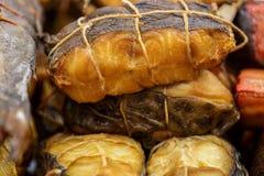 Verschiedene geräucherte Fische gebunden mit einer Aderpresse, vorbereiteter geschmackvoller Meeresfrüchtehintergrund, Makro Stockfotografie