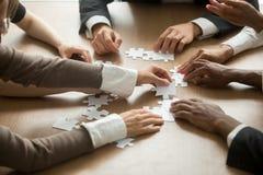 Verschiedene Geschäftsleute, die in zusammenbauendem Puzzlespiel, Teamwork s helfen stockfoto