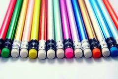 Verschiedene geschärfte bunte Bleistifte und Radiergummis Lizenzfreie Stockfotografie