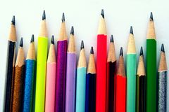 Verschiedene geschärfte bunte Bleistifte und Radiergummis Stockfotografie