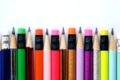 Verschiedene geschärfte bunte Bleistifte und Radiergummis Lizenzfreie Stockfotos