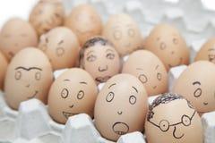 Verschiedene Gesichtsausdrücke gemalt auf braunen Eiern im Eierkarton Stockbild