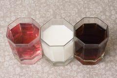 Verschiedene Getränke in drei Gläsern auf dem Hintergrund eines Leinenvorsprunges Stockfotos
