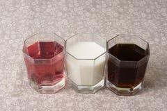 Verschiedene Getränke in drei Gläsern auf dem Hintergrund eines Leinenvorsprunges Lizenzfreie Stockfotografie