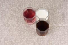 Verschiedene Getränke in drei Gläsern auf dem Hintergrund eines Leinenvorsprunges Stockfoto