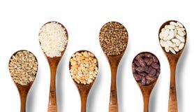 Verschiedene Getreide und Bohnen auf hölzernen Löffeln Stockfoto