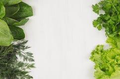 Verschiedene grüne Garben grünt für Frühlingssalat auf weißem hölzernem Hintergrund, Draufsicht, dekorativer Rahmen Lizenzfreies Stockbild