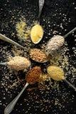 Verschiedene Grützen, Getreide Verschiedene Arten von Grützen auf Löffel auf einem schwarzen Hintergrund, Draufsicht Stockbild
