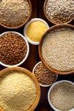 Verschiedene Grützen, Getreide Verschiedene Arten von Grützen in den Schüsseln auf einem hölzernen Hintergrund, Draufsicht, Absch Stockfotografie