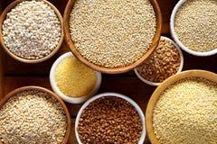 Verschiedene Grützen, Getreide Verschiedene Arten von Grützen in den Schüsseln auf einem hölzernen Hintergrund, Draufsicht, Absch Lizenzfreie Stockbilder