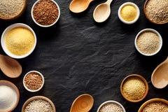 Verschiedene Grützen, Getreide Verschiedene Arten von Grützen in den Schüsseln auf einem schwarzen Hintergrund, Draufsicht Stockbilder