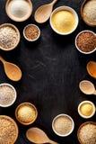 Verschiedene Grützen, Getreide Verschiedene Arten von Grützen in den Schüsseln auf einem schwarzen Hintergrund, Draufsicht Stockfotos