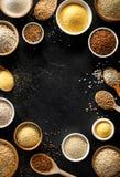 Verschiedene Grützen, Getreide Verschiedene Arten von Grützen in den Schüsseln und auf Löffel auf einem schwarzen Hintergrund, Dr Stockfotos