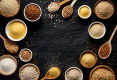 Verschiedene Grützen, Getreide Verschiedene Arten von Grützen in den Schüsseln und auf Löffel auf einem schwarzen Hintergrund, Dr Lizenzfreie Stockfotos