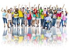 Verschiedene Gruppe hohe Schüler mit den Armen angehoben Lizenzfreie Stockfotografie