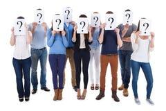 Verschiedene Gruppe von Personen, die Fragenzeichen hält Lizenzfreie Stockfotografie