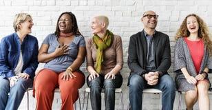 Verschiedene Gruppe von Personenen-Gemeinschaftszusammengehörigkeits-sitzendes Konzept stockfotos