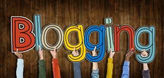 Verschiedene Hände, die das Blogging Wort halten Stockfoto