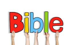 Verschiedene Hände, welche die Wort-Bibel halten lizenzfreie stockfotos