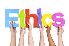 Verschiedene Hände, welche die Wort-Ethik halten Stockfotos