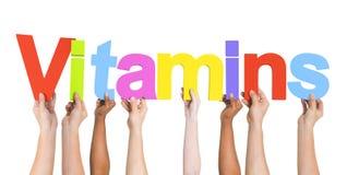 Verschiedene Hände, welche die Wort-Vitamine halten lizenzfreie stockfotografie