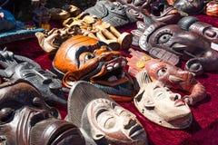 Verschiedene hölzerne asiatische oder afrikanische Masken im Verkauf an der Flohmarkt, draußen Lizenzfreie Stockfotografie