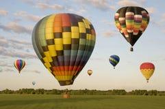 Verschiedene Heißluftballone, die über ein Feld schwimmen Lizenzfreies Stockbild