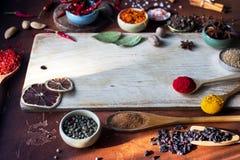 Verschiedene indische Gewürze in den hölzernen Löffeln, in den Samen, in den Kräutern und im nuts und leeren hölzernen Brett Lizenzfreie Stockfotos