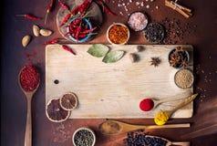 Verschiedene indische Gewürze in den hölzernen Löffeln, in den Samen, in den Kräutern und im nuts und leeren hölzernen Brett Lizenzfreies Stockfoto