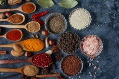 Verschiedene indische Gewürze, Nüsse und Kräuter in den hölzernen Löffeln und in den Metallschüsseln Stockfoto