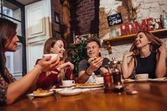 Verschiedene junge Leute, die plaudernd und lächelnd in einem Café zu Mittag essen Stockfotos