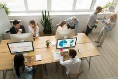 Verschiedene junge und ältere zusammenarbeitende Unterhaltung der Büroangestellten, t Stockbilder