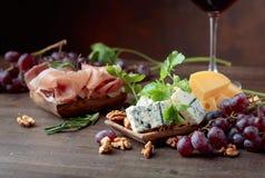 Verschiedene Käse, Trauben und Prosciutto lizenzfreies stockfoto